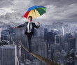 Leinwandbild Motiv Equilibrist businessman walk on a rope with umbrella over the city. Concept of overcome the problems and positivity