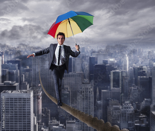 Equilibrist businessman walk on a rope with umbrella over the city. Concept of overcome the problems and positivity