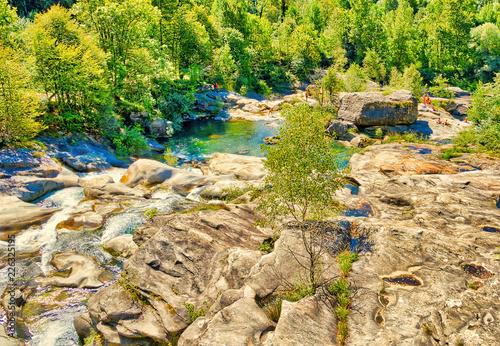 Foto Murales Fiume che scorre sulle rocce tra le Alpi