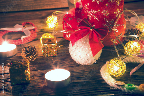 Christmas lights and decorations over wooden background. New Year Baubles over old Wood table. Xmas decoration. Vintage border art design