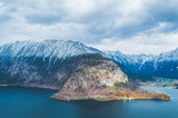 Austrian Alps covered with snow with a beautiful calm lake and cloudy sky on the background