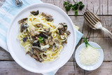 Tagliatelle with cream and forest mushrooms sauce in a white plate on a wooden background. Rustic style.