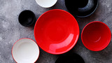 Collection of empty colorful decorative ceramic bowls on grey stone background. Top view, flat lay.