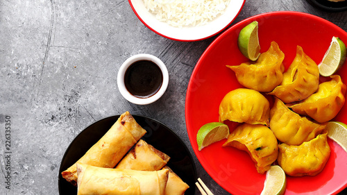 Top view of Chinese food set. Dumplings, boiled rice, spring rolls, fortune cookies on stone table. - 226335350