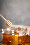 Pouring aromatic honey into jar, closeup. Honey in glass jars and honeycombs wax on wooden background. Wooden stick , instruments