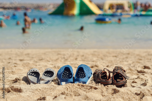 4572d465c9d53 Three pairs of summer shoes are laying on the sand near the sea ...