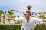 European boy is playing with his father at the green lawn. They are smiling and imitating planes. - 226347353