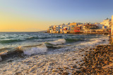 Sunset view of the famous pictorial Little Venice  in Mykonos island. Splashing waves over bars and restaurants of Mykonos old town, Cyclades, Greece. - 226349357