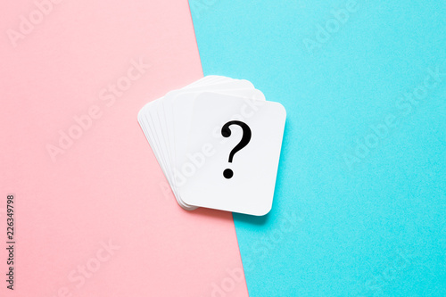 Card of question mark on pastel pink and turquoise blue background. Soft light color. Teenagers issues. Boys and girls or men and women problems and solutions concept. Couples relationships.