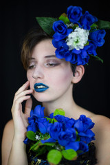 Sensual young woman touching face and looking away with blue flowers composition   © pablobenii