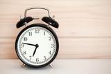 Vintage alarm clock is on white bedside table