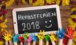 """Leinwandbild Motiv in bunten Farben angemalte Kinderhände vor herbstlich dekorierter Kreidetafel und der Aufschrift """"Herbstferien 2018 :)"""""""