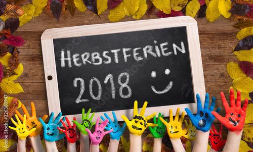 """Leinwanddruck Bild in bunten Farben angemalte Kinderhände vor herbstlich dekorierter Kreidetafel und der Aufschrift """"Herbstferien 2018 :)"""""""