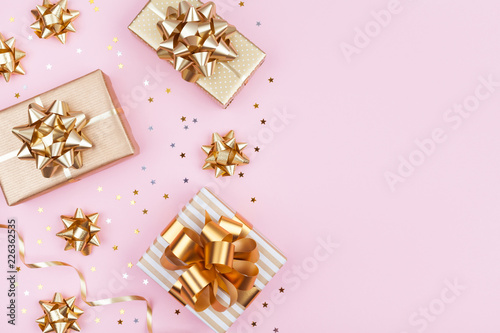 Leinwandbild Motiv Fashion gifts or presents boxes with golden bows and star confetti on pink pastel table top view. Flat lay composition for birthday, christmas or wedding.