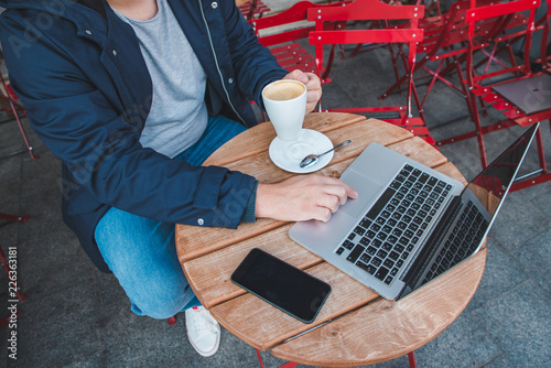 Foto Murales overhead view woman holding cup of coffee while working on laptop