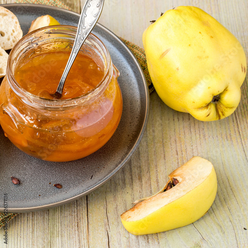 A small glass jar of jam and a fresh ripe quince fruits on an old table.  - 226371136
