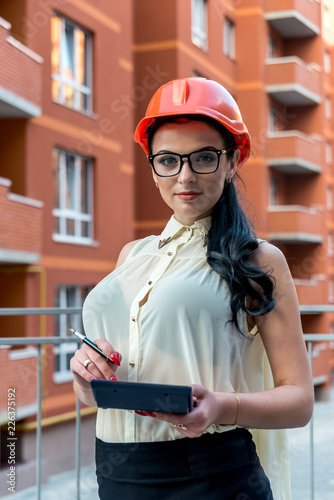 Beautiful brunette in helmet on construction site with calculator - 226375192