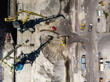 Construction cranes on river's bank by drone
