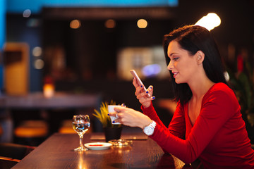 Beautiful young woman suing smartphone and drinking coffee in a cafe