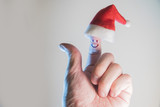 Finger face with smile in Santa hats on white  background. Happy celebrating   concept for Christmas day - 226385502