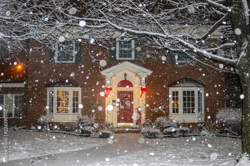 Snowfall on beautiful brick house with columns and bay windows with Christmas tree light up and red sled and wreath on porch © Susan Vineyard