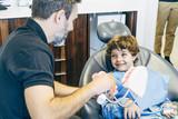 Dentist teaching little boy teeth in dental clinic