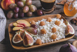 Homemade cottage cheese , raspberries,figs , peach, honey. Healthy breakfast, coffee. on serving board over rustic wooden