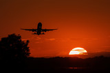 SIlhouette of airplan take off at sunset with red sky in background
