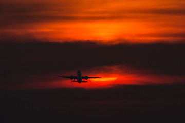 Air plane taking off at sunset near to the sun with beautiful red cloud in background