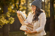 beautiful woman in a cap and glasses is holding a pile of books on the background of autumn forest