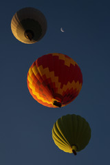 View from bellow a colorful hot air ballloon near the moon with beautiful blue sky in background
