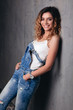 Curly model in a jeans jumpsuit, smiling model