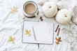 Autumn breakfast in bed composition. Blank cards, notebook mockup. Cup of coffee, white pumpkins, sweater, oak leaves and gypsophila flowers on linen background. Thanksgiving, Halloween. Flat lay. Top
