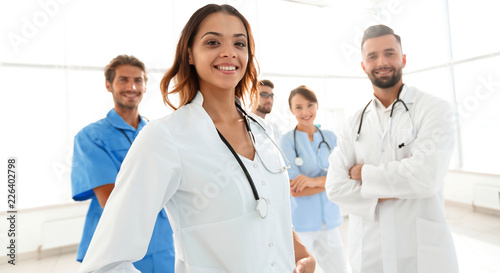 Foto Murales Attractive female doctor with medical stethoscope in front of medical group