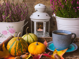 Close up view of vintage blue cup of coffee in a tray with pumpkins and leaves, calluna flowers and a lantern with a lit candle with wooden background. Halloween or autumn background