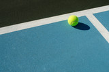Tennis ball rests on blue tennis court - 226412719