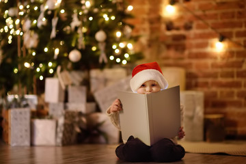 Little boy reading a magic book in decorated cozy living room