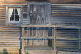 Rustic entrance to old wood cabin with unfinished clapboard siding, a window, a door, and a stoop with ramp and handrail. - 226435543