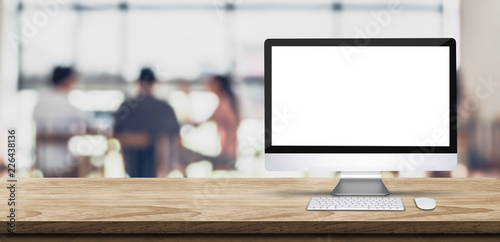 Blank screen desktop computer on wooden table top with blur people working at creative office bokeh background,Mock up for display or montage of design.