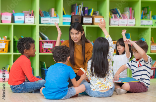 Leinwandbild Motiv Asian female teacher teaching and asking mixed race kids hand up to answer in classroom,Kindergarten pre school concept.