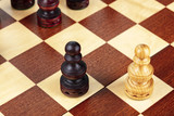 Two pawns on a chessboard, a metaphor for a conflict or a challenge