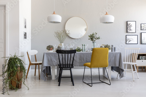Black And Yellow Chair At Table In White Dining Room Interior With Plants Lamps