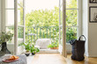 Leinwanddruck Bild - Open glass door from a living room interior into a city garden on a sunny balcony with green plants and comfy furniture