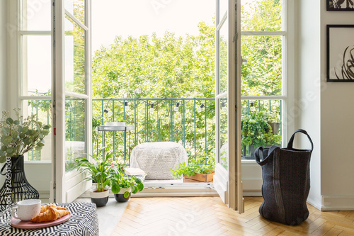Leinwanddruck Bild Open glass door from a living room interior into a city garden on a sunny balcony with green plants and comfy furniture