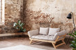 Quadro Grey sofa between plant and black lamp in wabi sabi loft interior with red brick wall. Real photo
