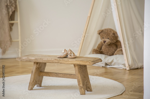 Wooden stool with shoes on white round rug in kid's room interior with plush toy in tent. Real photo