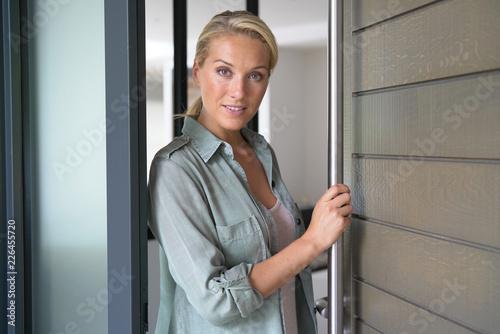 Leinwanddruck Bild Blond woman welcoming people at entrance front door