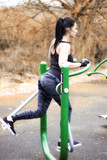 A young, athletic woman in outdoor sports using outdoor exercisers, autumn