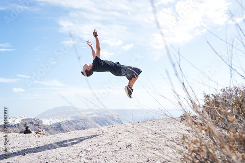 Leinwandbild Motiv Mann macht Parkour und springt einen Salto vor der Küste Santorins