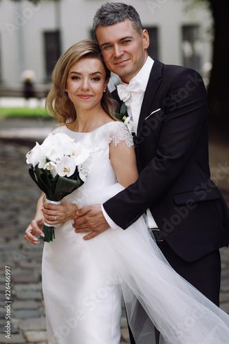 Leinwandbild Motiv Groom in black tuxedo hugs tender stunning bride while they stand on the street of old European town